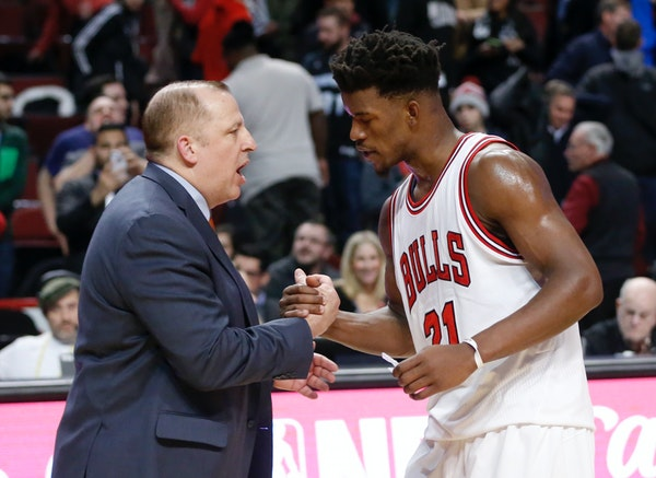 Minnesota Timberwolves head coach Tom Thibodeau, left, shakes hands with his former player Chicago Bulls' Jimmy Butler after an NBA basketball game Tu