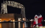 Santa Clause waved towards a child looking down on the parade from the DECC on Friday night. No spectators were allowed on the street but one family f