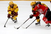 The University of Minnesota Gopher's Emily Oden (21) and Gracie Ostertag (6) battle for a loose puck with Ohio State's Gabby Rosenthal during the 1s