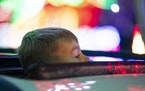 A young boy stuck his head out of the sunroof as his family's car passed through the first tunnel of lights in Bentleyville on Saturday.