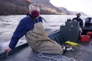 Peter Sorensen sat against the hull of his boat as Jeff Whitty, a research biologist, steered them down the Mississippi River towards their target are