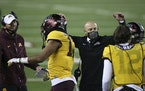 Minnesota head coach P.J. Fleck pats Minnesota wide receiver Seth Green's (17) helmet in celebration after Green scored a touchdown during the first h