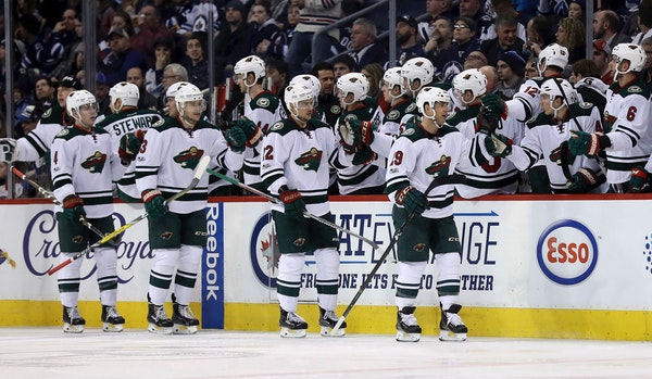 Minnesota Wild players celebrate a goal by Jason Pominville (29) against the Winnipeg Jets during the second period of an NHL hockey game Tuesday, Feb