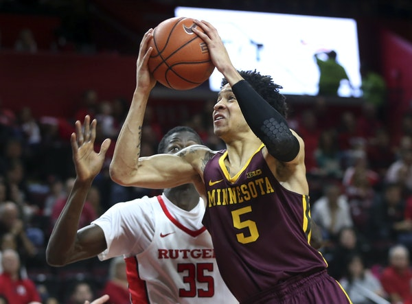 Gophers freshman guard Amir Coffey took the ball to the basket against Rutgers' Issa Thiam in the first half Saturday.