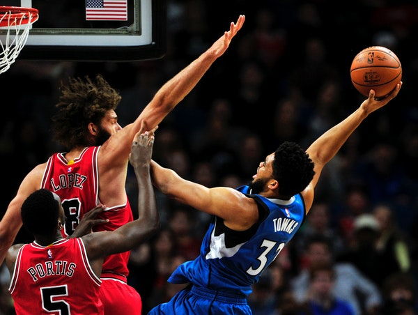 Minnesota Timberwolves center Karl-Anthony Towns (32) shoots against Chicago Bulls' Bobby Portis (5) and Robin Lopez (8) during the first quarter of a