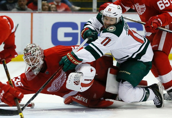 Minnesota Wild's Zach Parise (11) tries to take a shot on goal against Detroit Red Wings' Jimmy Howard (35) during the first period of an NHL hockey g