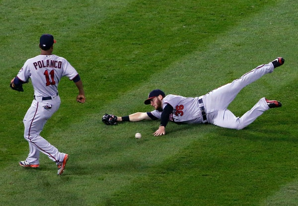 Minnesota Twins left fielder Robbie Grossman, right, cannot make the play on a single by Chicago White Sox's Melky Cabrera as shortstop Jorge Polanco,