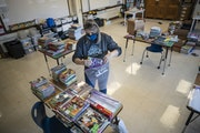 Teacher Gretchen Polkinghorne bagged donated books at Community of Peace Academy in St. Paul. Teenage sisters donated 600 children's books.