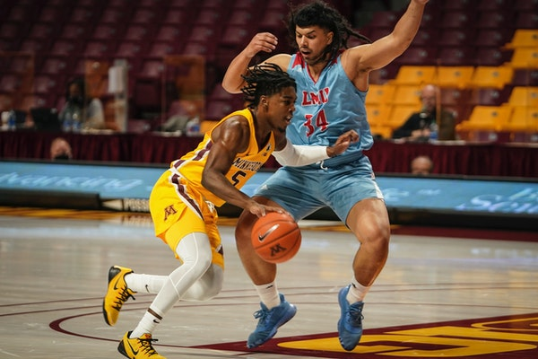 Gophers guard Marcus Carr pushed past Loyola Marymount University forward Keli Leaupepe in the first half of a game earlier this season.