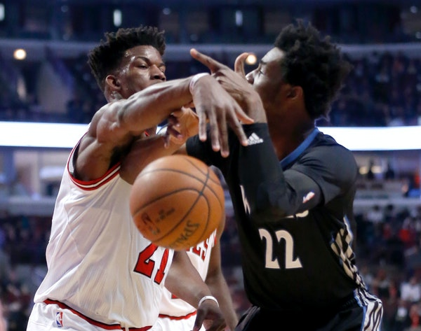 Chicago Bulls' Jimmy Butler, left, slaps the ball out of Minnesota Timberwolves' Andrew Wiggins' hands during the first half of an NBA basketball game