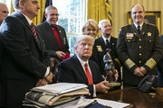 President Donald Trump holds a figurine given to him during a meeting with a group of sheriffs, in the Oval Office of the White House in Washington, F