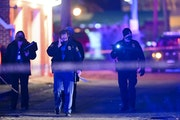 St. Paul Police officers and Bureau of Criminal Apprehension investigators walk near the scene of an earlier shooting in which St. Paul Police shot a