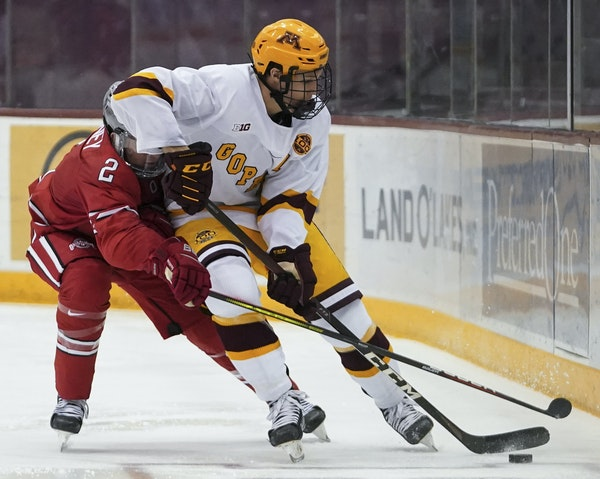 Ohio State Buckeyes Layton Ahac (4) and Minnesota Gophers Jackson LaCombe (2) fought for the puck in the third period. The Gophers won 4-1. ] RENEE JO