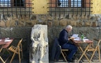 An ancient Roman marble statue sits among tables of a restaurant in the Garbatella neighborhood in Rome, Tuesday, Nov. 24, 2020. (AP Photo/Gregorio Bo