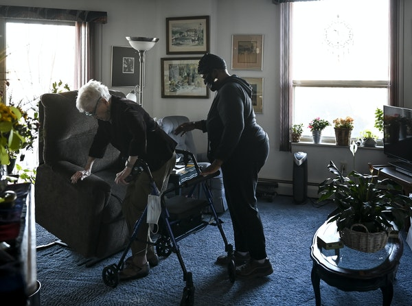 Personal caregiver Deborah Howe helped her 101-year old client, Polly Mann, move to her living room Friday afternoon.    ] AARON LAVINSKY • aaron.la