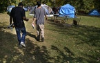 Newfound friends Brandon O'Neil Abrams, 31, left, and Brandon Harrison, 35, walk through a homeless camp at Logan Park where they are both living in t