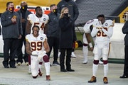 Members of the Washington Football Team react during the playing of the National Anthem before an NFL football game against the Pittsburgh Steelers, M