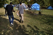 Brandon O'Neil Abrams, 31, left, and Brandon Harrison, 35, walked through Logan Park where they were both living in tents in October. Three encampme