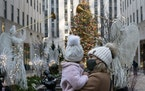 A woman holds her daughter as they look at the Rockefeller Center Christmas tree, on Dec. 3 in New York City.