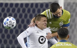 Seattle Sounders defender Shane O'Neill, back right, comes in over the top of Minnesota United midfielder Robin Lod during the first half of an MLS