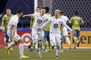 Minnesota United' Emanuel Reynoso, right, celebrates his goal against the Seattle Sounders with teammates Michael Boxall, left, and Jan Gregus during