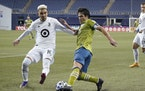Seattle Sounders midfielder Nicolas Lodeiro, right, kicks the ball in front of Minnesota United midfielder Emanuel Reynoso during the first half of an