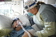 Kate Van Bergen, a nurse at North Memorial Health Hospital in Robbinsdale, leaned in to talk to Joe Bisson, 81, of Maple Grove, in the intensive care