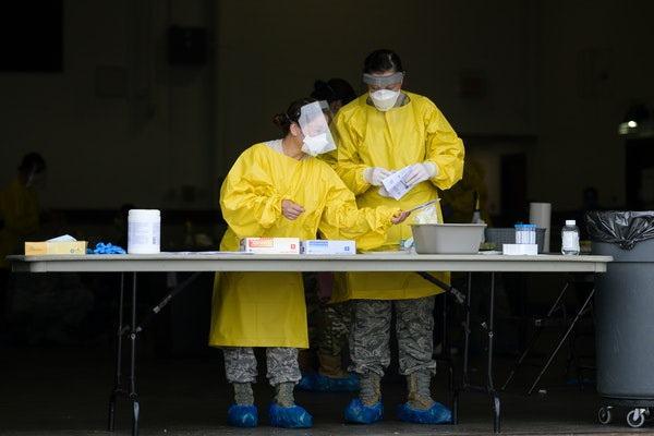 Elizabeth Santoro, left, and Kristin Anderson, medics with the Minnesota Air National Guard 133rd Medical Group, sanitized and prepared for their next