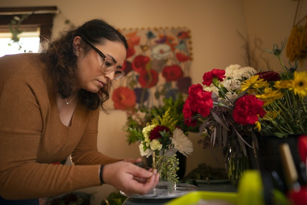 After she lost her job, Cindy Tlaiye and her husband moved and sold their car. She makes and sells bouquets to help with expenses.