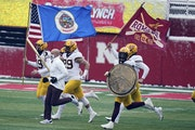 Minnesota head coach P.J. Fleck leads his players onto the field before the first half of an NCAA college football game against Nebraska in Lincoln, N