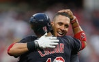 The Cleveland Indians' Francisco Lindor hugs teammate Michael Brantley after Brantley hit a double to score Lindor for a 2-1 win in 10 innings again