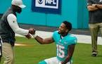 Miami Dolphins head coach Brian Flores greets running back Lynn Bowden (15) before an NFL football game against the Cincinnati Bengals, Sunday, Dec. 6