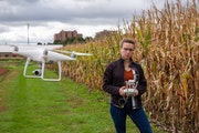 University of Minnesota Agronomy and Plant Genetics graduate student Dorothy Kirsch (above right) and her field drone on St. Paul campus. She is worki