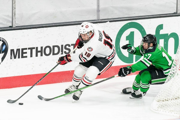 St. Cloud State's Brendan Bushy, left, fended off North Dakota's Riese Gaber on Wednesday night in Omaha.