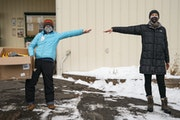 "Health care officials Andrea Orest and Grace Grinager stood ""one moose apart"" in Grand Marais."