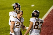 Minnesota's Josh Aune (29) and Austin Henderson walk off the field after Wisconsin defeated them in overtime on Saturday. The Gophers finished the r