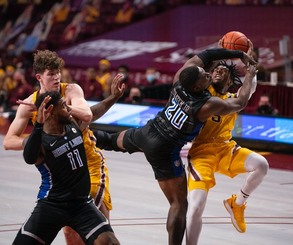 Gophers guard Marcus Carr tried to get a first half shot off with St. Louis guard Fred Thatch Jr. draped over him.