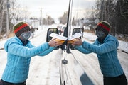 Andrea Orest walked along a line of cars in Grand Marais to hand out free at-home COVID-19 saliva tests on Dec. 16.