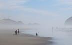 People walk on the beach at Tierra del Mar, Ore.