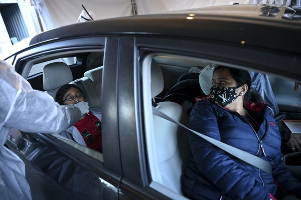 Nidhi Joshi, right, watched as her 9-year old son, Bhruv was tested for COVID-19 on Friday, Dec. 4, at North Memorial's drive-up testing site.    ]