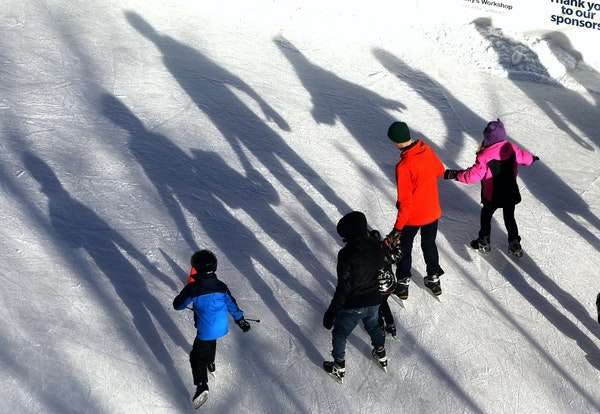 Skaters cast long shadows in the slanting afternoon sun.