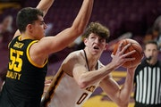 Minnesota center Liam Robbins eyed the basket as Iowa center Luka Garza defended in the first half Dec. 25.