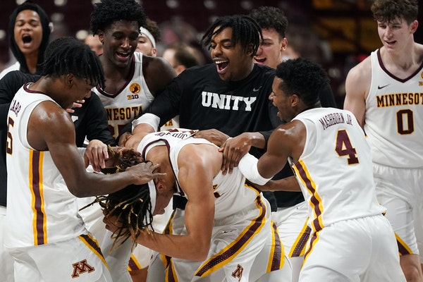 Minnesota forward Brandon Johnson (23) was mobbed by his teammates on the court after his multiple three point shots helped them beat the Iowa Hawkeye