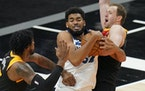 Wolves star Karl-Anthony Towns pulled down a rebound between Utah's Derrick Favors, left, and Joe Ingles during the second half Saturday night.