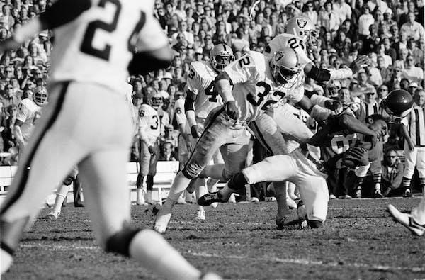 Vikings receiver Sammy White lost his helmet as two Raiders defenders hit him during Super Bowl XI in Pasadena, Calif., on Jan. 9, 1977.