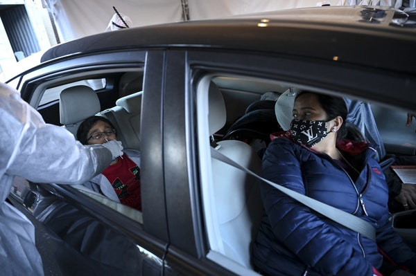 Nidhi Joshi, right, watched as her 9-year-old son Bhruv was tested for COVID-19 at a drive-up testing site at North Memorial Medical Center in Robbins