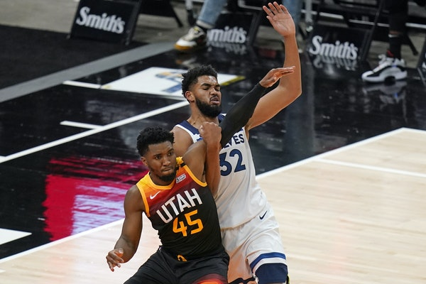 Utah Jazz guard Donovan Mitchell (45) and Minnesota Timberwolves center Karl-Anthony Towns (32) battle for position under the boards Saturday.