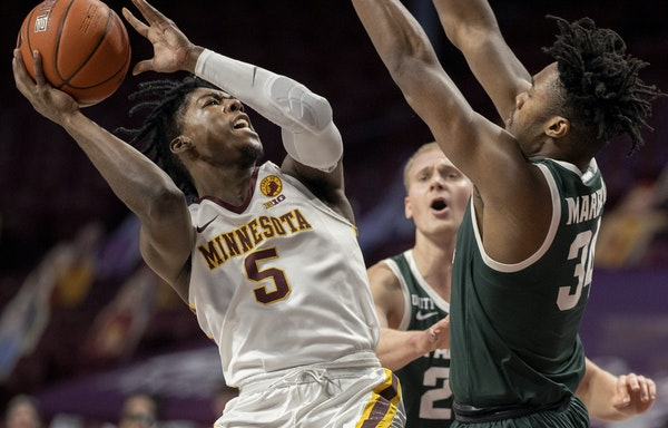 Above, Marcus Carr (5) of Minnesota attempted a shot while defended by Julius Marble II (34) of Michigan State in the first half. Top, Liam Robbins (0
