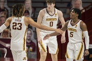 Marcus Carr (5) celebrated with Brandon Johnson (23) and Liam Robbins (0) during Monday's victory against Michigan State.