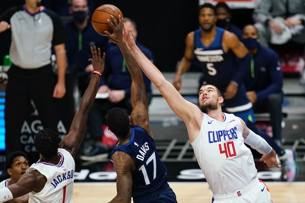 Los Angeles Clippers guard Reggie Jackson, left, and center Ivica Zubac and Timberwolves forward Ed Davis reach for a rebound during the first quarter